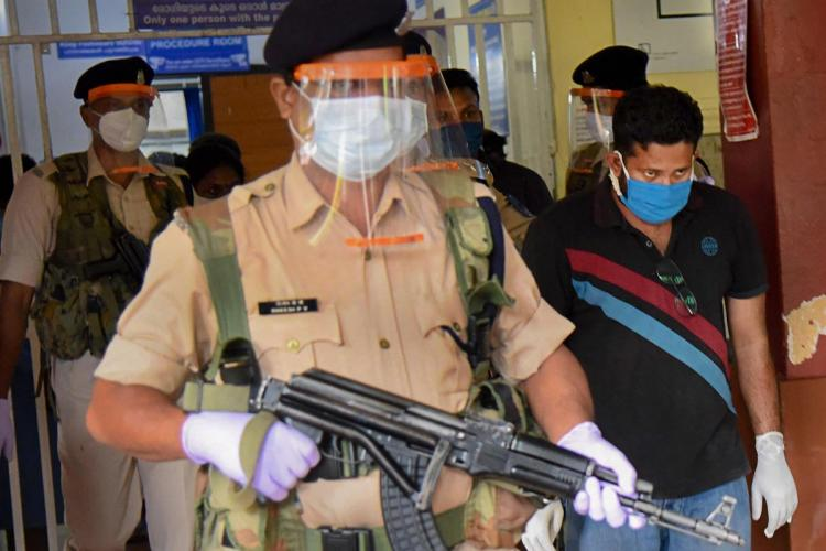 Gold smuggling accused Sandeep Nair along with NIA officials who are escorting him carrying rifles