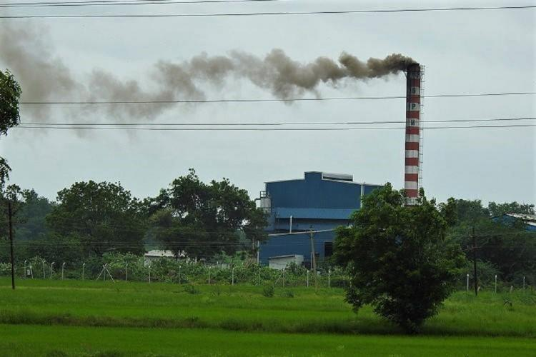 Smoke billows from a factory in Sangareddy district in Telangana in the backdrop of an agricultural field