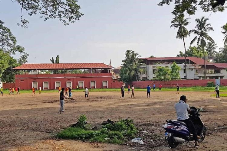 Children playing at the Santa Cruz ground in Fort Kochi as a man on a parked two-wheeler watches in the foreground
