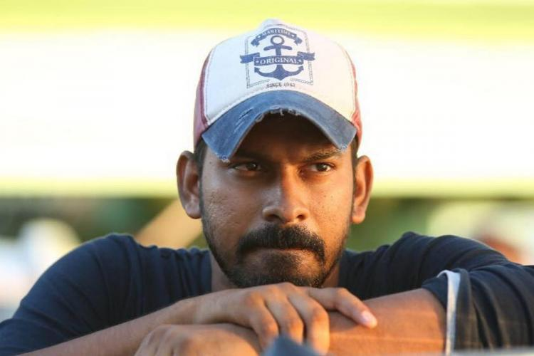 Director Santhosh wearing a hat