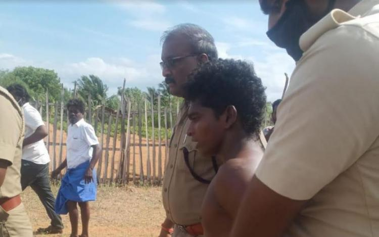 Two police officers are taking the accused to the police station in Sathankulam