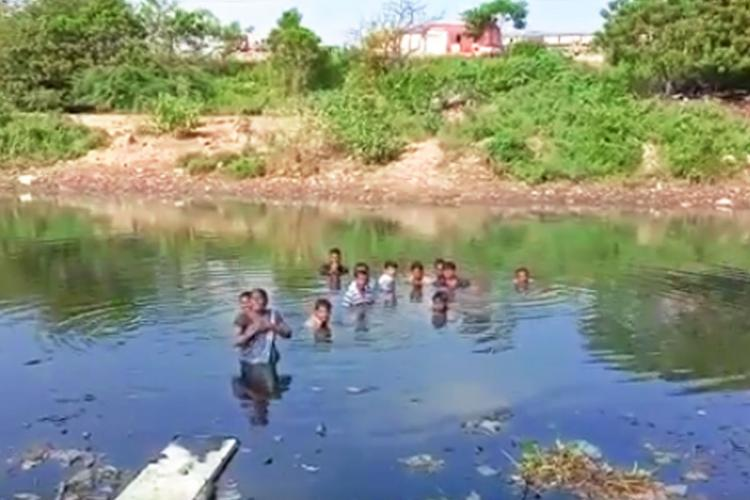 Chennais Park Town residents stand in Cooum waters and protest eviction