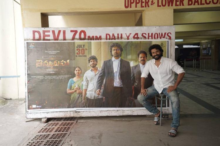Actor Satyadev in front of his movie Thimmarusu poster at Devi 70mm theatre in Hyderabad