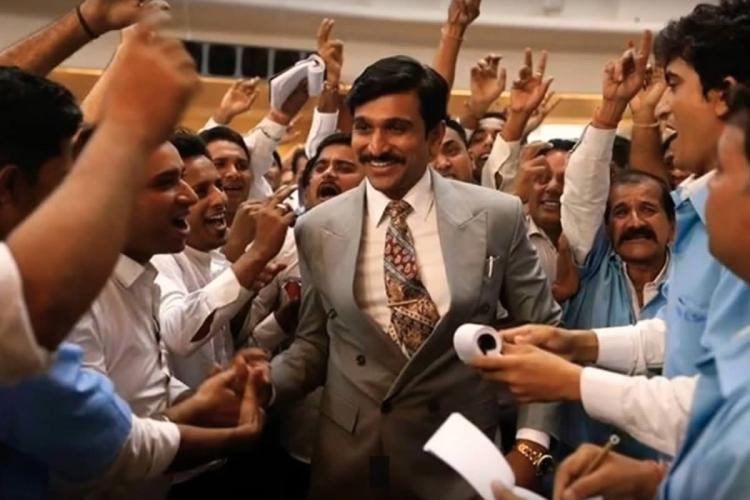 A scene from Scam 1992 The Harshad Mehta Story showing actor Pratik Gandhi as Harshad Mehta wearing a grey suit and smiling He is surrounded by several men who seem to be cheering him some with their hands raised