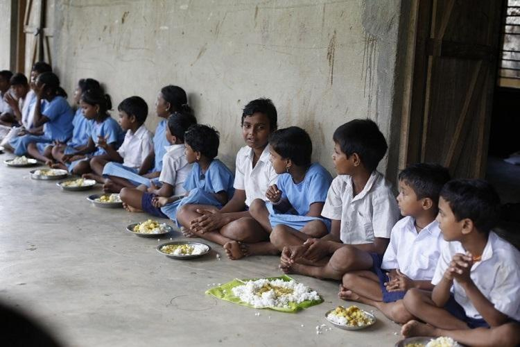A representative image of school children sitting in line eating lunch served under the midday meals scheme