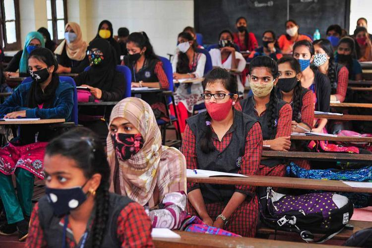 A classroom full of students wearing masks and seated with social distance