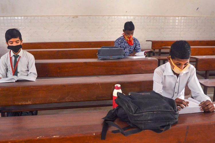 School students sitting far away from each other in classroom after schools reopened