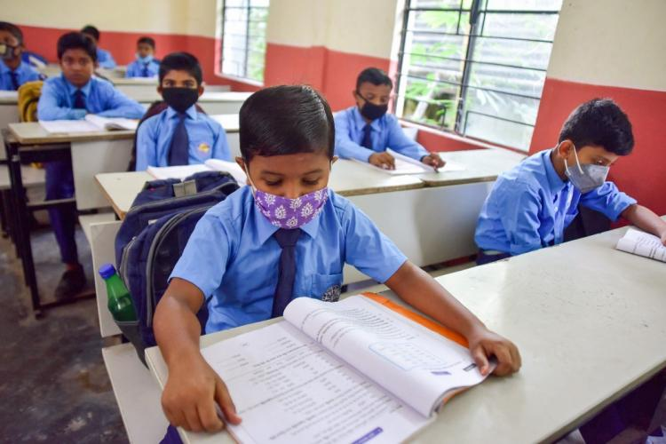 Children reading text books while wearing face masks and seated in benches in school uniform