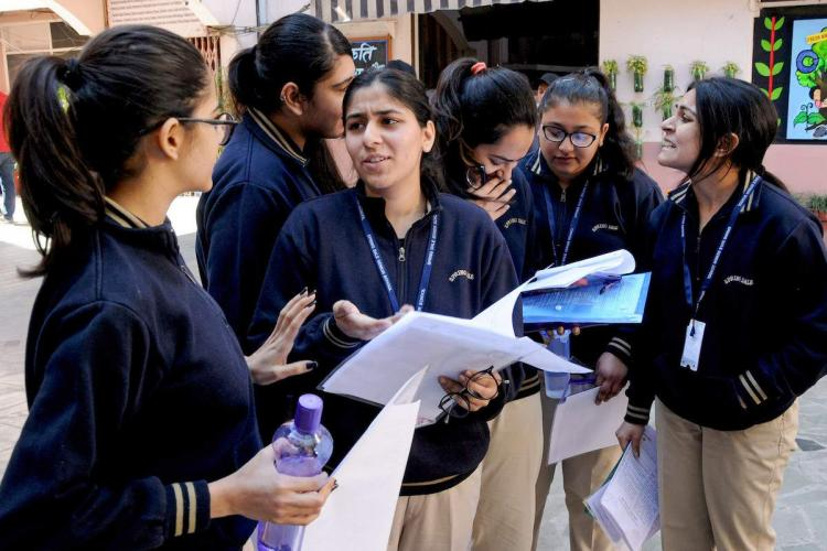 School students discuss answers after exam in India