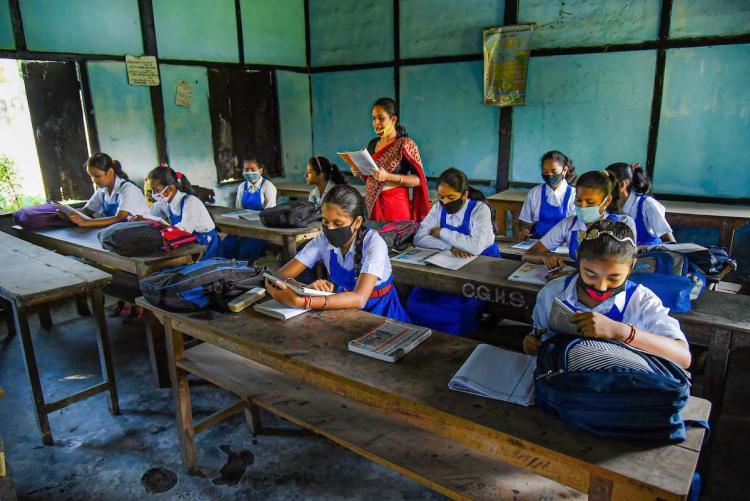 A teacher teaching kids who are sitting away