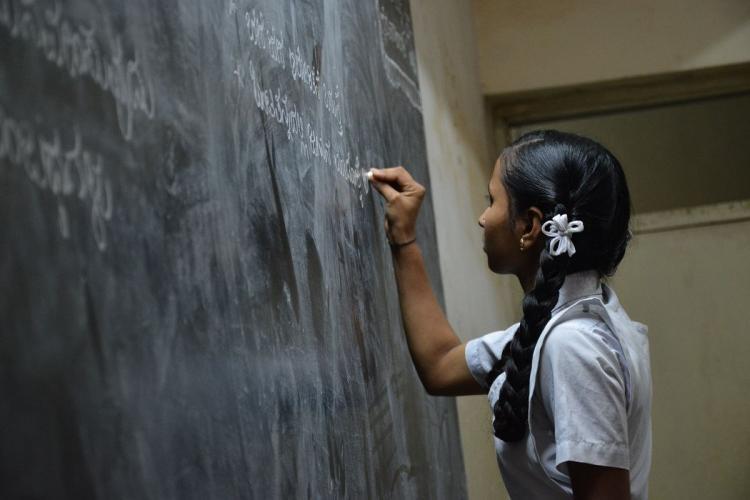 A schoolgirl writing on a blackboard