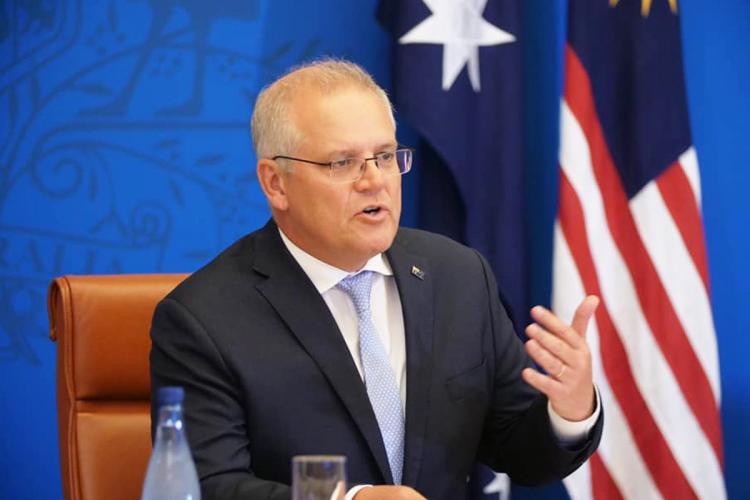 Australian Prime Minister Scott Morrison gestures while speaking to the media