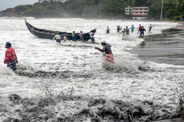 Fishermen pulling canoe back to the shore