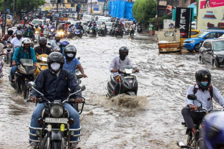 People struggling to ride through an inundated area in Secunderabad