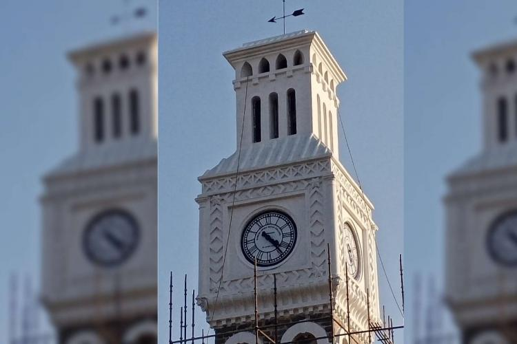 A close up of the white clock tower against the blue sky