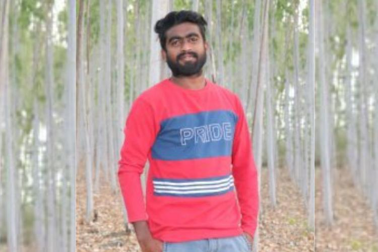 Prasad from Seethanagaram wearing a red and blue full sleeved t shirt while standing against tall trees