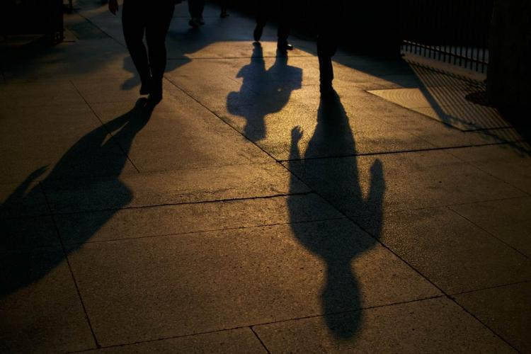 Four long shadows on the pavement created by the rays of a setting sun. A few pair of feet are also visible