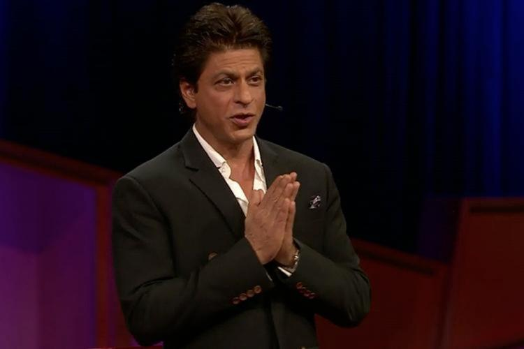 Shah Rukh wearing a black suit is seen talking to an audience