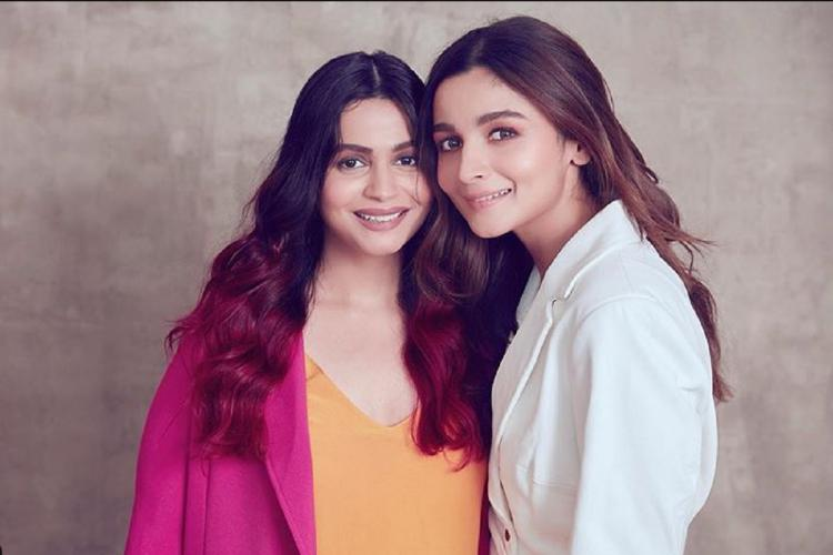 A photo of Shaheen and Alia Bhatt Shaheen is wearing an orange and pink top and Alia is wearing a white shirt