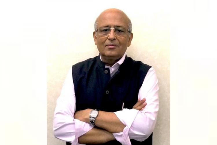 Virologist Shahid Jameel wearing a white shirt and a black Nehru jacket and looking into the camera with his arms crossed