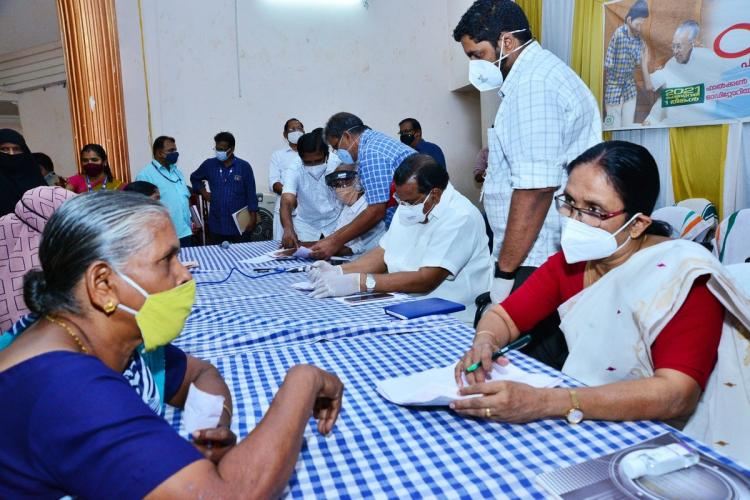 Kerala Health Minister KK Shailaja interacting with a woman Both are sitting across each other at a desk Others are also seen interacting with people All are wearing masks