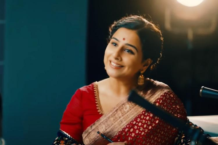 Vidya Balan talking and smiling in a still from film Shakuntala Devi She is sitting and wearing a red saree