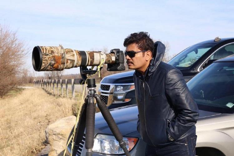 Director Shankar looking through a wide zoom lens camera
