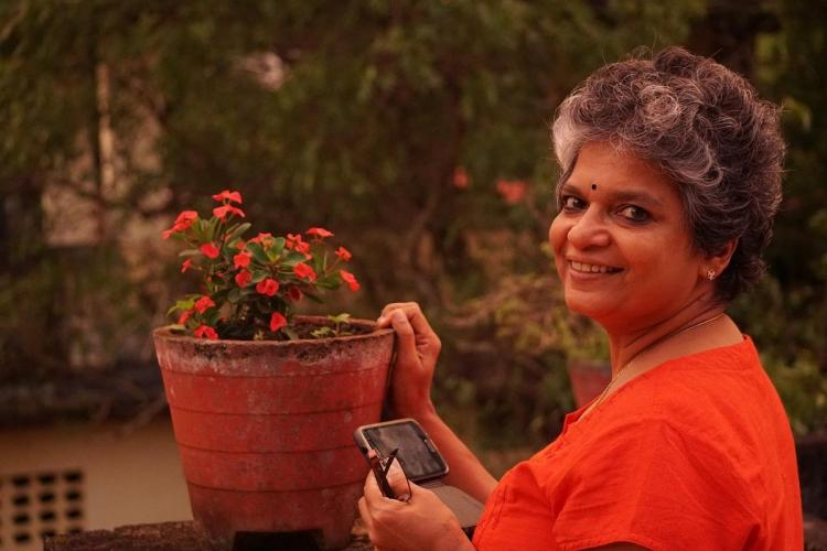 Sheena in a red top tends to a plant in a pot and smiles