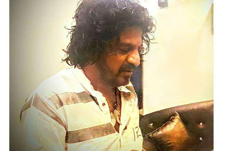 Actor Shiva Rajkumar in Kannada movie Shivappa. He is seen sporting what seems to be a jail inmate's uniform, with his hair looking unkempt. He is also seen wearing a chain with a tiger tooth pendant.