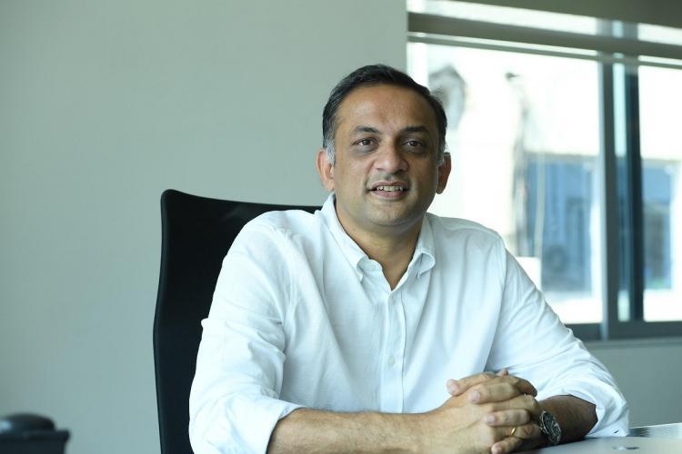 A file photo of Shobu Yarlagadda shows him sitting at a desk wearing a white shirt