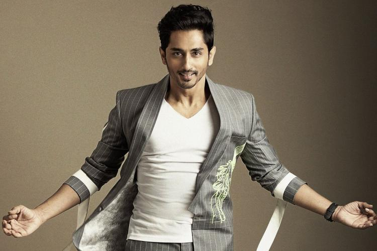 Siddharth in a grey suit and a white shirt posing for a picture