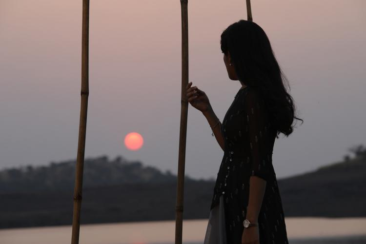A woman stands overlooking a sunset