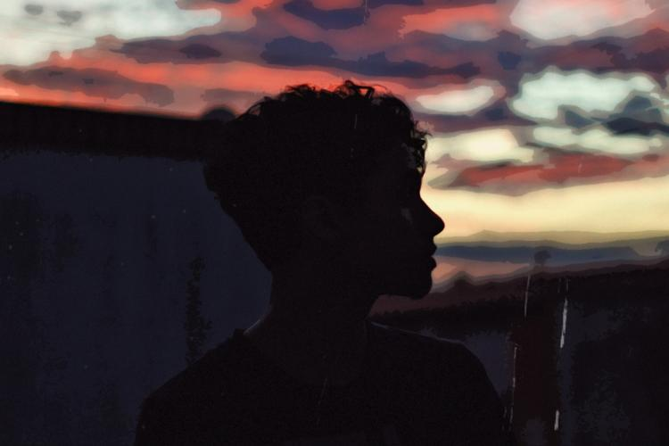 Silhouette of a person against dark skies as they look beyond the horizon to the right of the frame