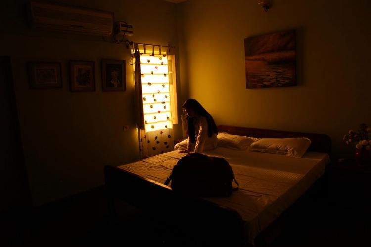 In this silhouette a woman is seen sitting on the bed A backpack is kept on the bed