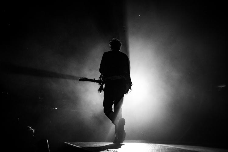 A silhouette of a singer and performer with a guitar on stage