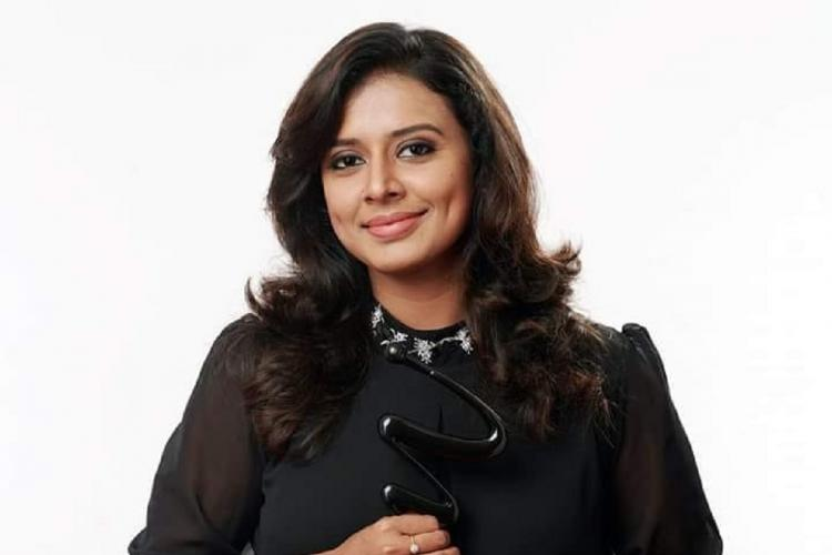 Singer Sithara in a black outfit stands holding an award Her hair hangs losely around her shoulders and she is smiling
