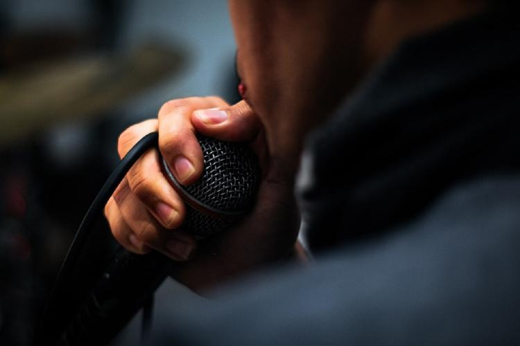 A man singing into a mic holding the cable