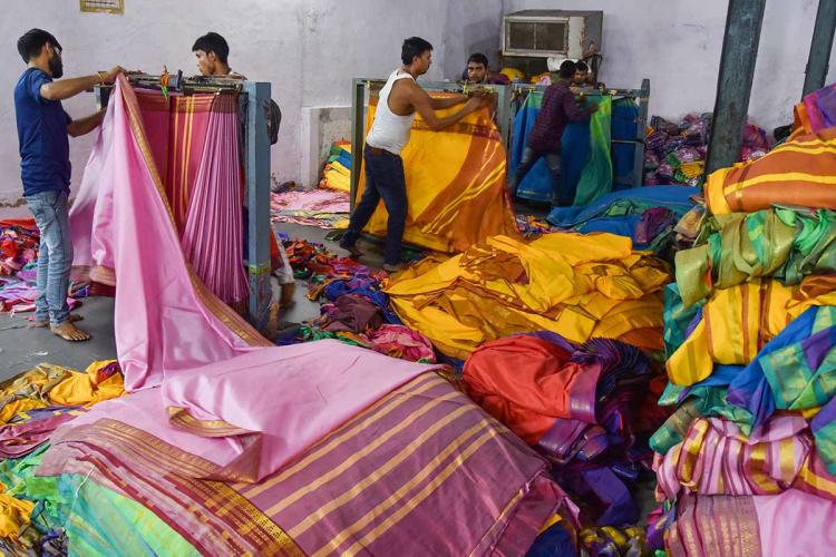Workers in a textile unit working on Bathukamma saris