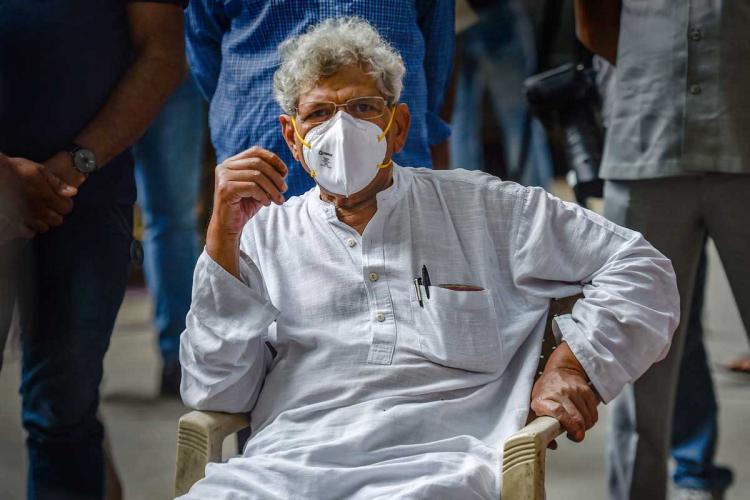Sitaram Yechury wearing a mask and sitting