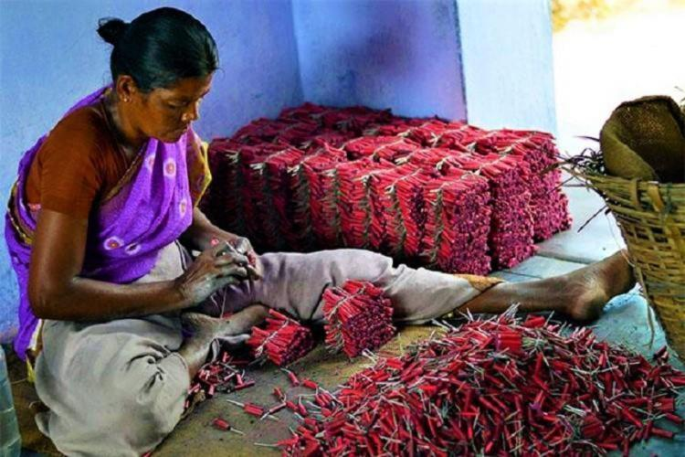 A women cracker maker rolling the crackers in Sivakasi