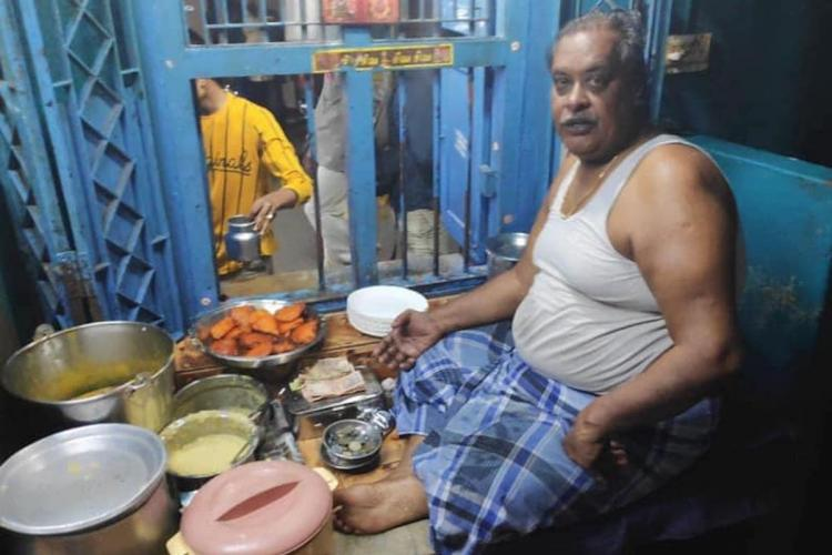 Man in blue lungi and banian sitting inside a shop selling snacks