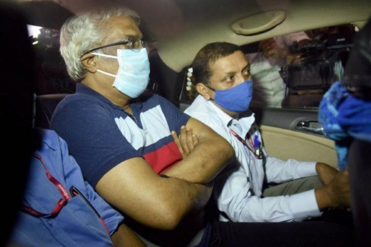 Sivasankar in a blue t shirt has a mask on his face and his hands folded sitting inside a vehicle with other men