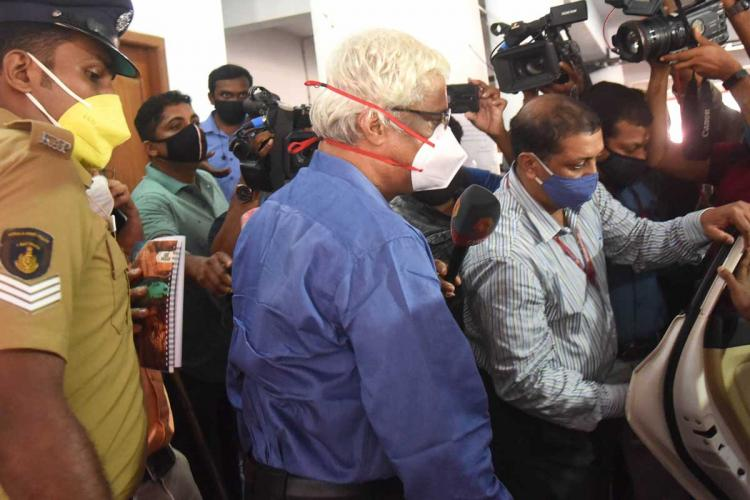 Sivasankar IAS heading to enter his car along with investigation officers Media personnel in the background