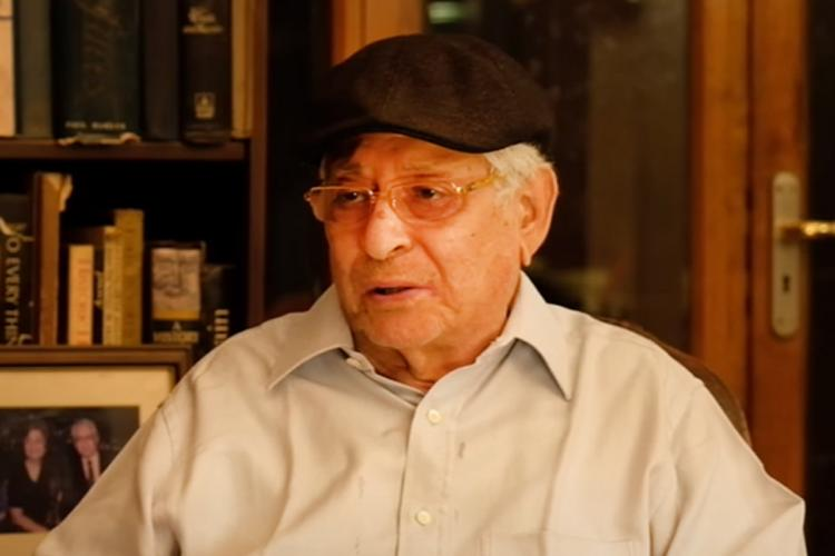 Soli Sorabjee wears a cap and looks to the left with a showcase of books behind him