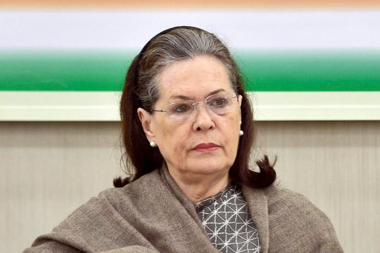 Sonia Gandhi sitting in the backdrop of INC flag