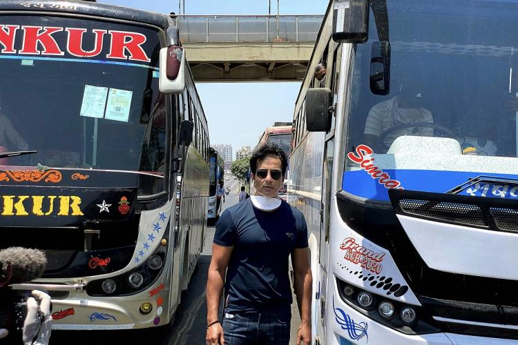 Actor Sonu Sood standing in front of two buses which he arranged to help migrant workers reach home during the lockdown