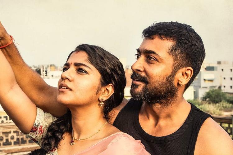 A scene from the movie Soorarai Pottru Suriya is seen in a black vest Aparna Balamurali is seen in a sari Both are looking up in the sky