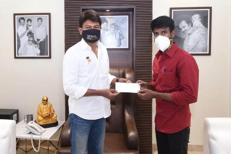 Soori is handing over a cheque to Udhayanidhi Stalin