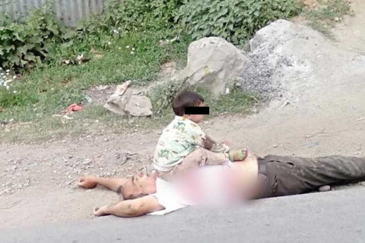 Child in Jammu and Kashmir sitting on the body of his grandfather who was killed in a terror attack