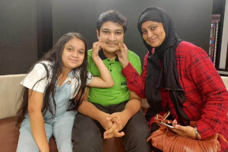 NEET 2020 topper Soyeb Aftab with his mother and sister pulling his cheeks